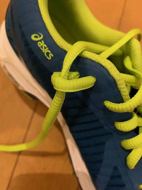 アシックスの靴の写真です。靴ひもの結び方を説明しています。靴にある謎の2つの穴の使いかたの説明です。