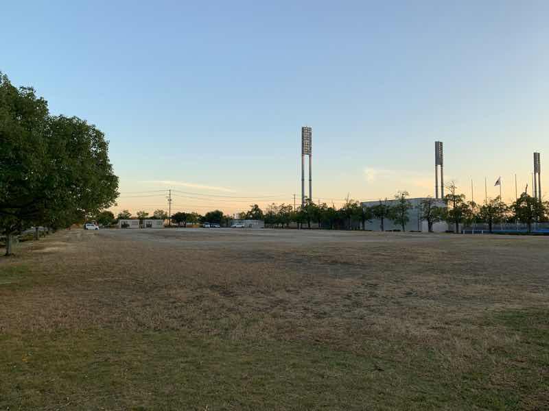 かかみがはらシティマラソンの駐車場の写真です。 大会会場の川崎重工ホッケースタジアムのとなりでとても近い場所です。整地はされていますがアスファルトではなく土の駐車場です。