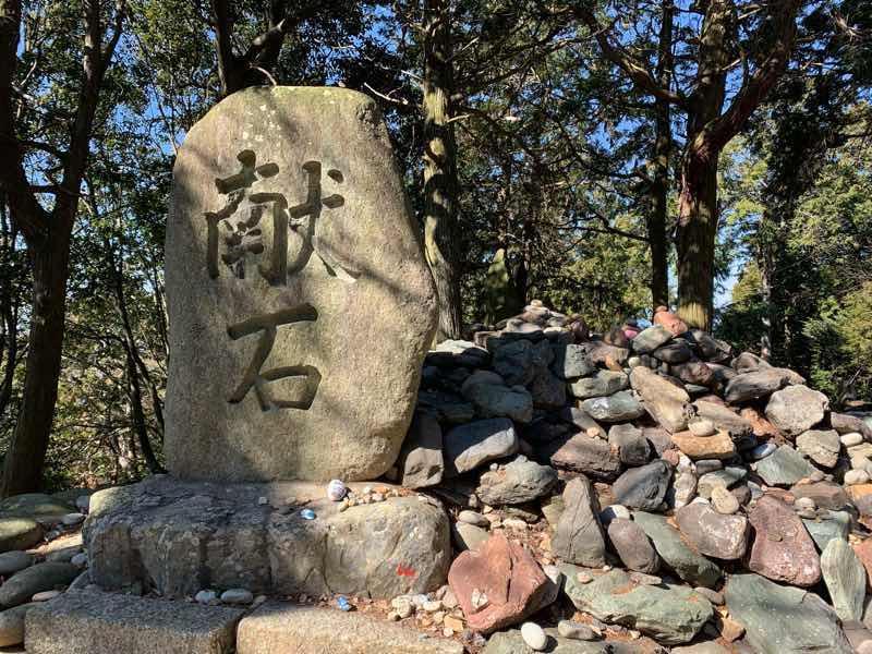 山頂の様子です。大人の人の身長くらいある献石があり、その周りには願い事の書かれた石が多数献石されています。