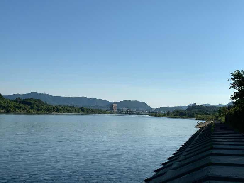 暑さ回避のため早朝に河川敷を走った時の木曽川の様子です。遠くに犬山城が見えます。また、天気もよく、雲一つない空です。