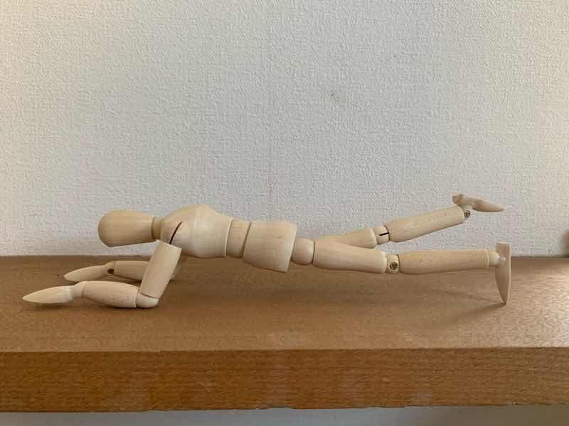 体幹トレーニングの基本的なトレーニングとしての片足プランク(ワンレッグプランク)をしている人形の写真です。