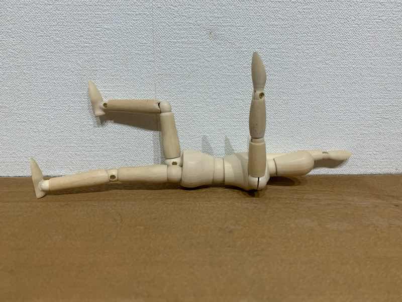 体幹トレーニングの基本的なトレーニングとしてのデッドバグをしている人形の写真です。